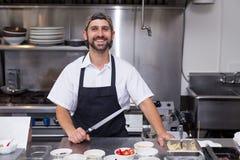 Een gelukkige glimlachende mannelijke chef-kok in een restaurantkeuken die een chef-koksmes houden royalty-vrije stock foto