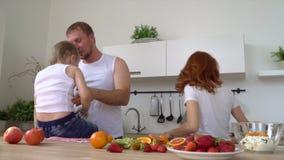 Een gelukkige hechte familie speelt ongeveer wanneer het koken van een ontbijt in de keuken Al familie maakt een ontbijt in keuke stock videobeelden