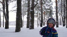 Een gelukkige het lachen kindlooppas naar een bewegende stedikam camera in een bos of een park Een kleine jongen speelt het doorn stock footage