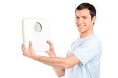 Een gelukkige jonge mens die een gewichtsschaal houdt Royalty-vrije Stock Foto's