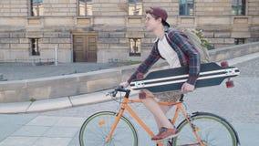 Een gelukkige kerel die een fiets met een skateboard in van hem berijden dient stedelijk gebied in stock footage