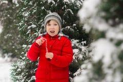 Een gelukkige kindjongen houdt traditionele Kerstmis spiraalvormig gestreept r royalty-vrije stock afbeeldingen