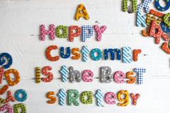 Een gelukkige klant is de beste strategietekst van kleurrijke brieven op witte achtergrond, het concept van de klantenzorg stock foto