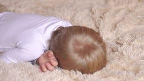 Een gelukkige kleine jongen ontwaakt in de ochtend in bed stock footage