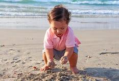 Een gelukkige kleine jongensspelen met zand in het strand stock afbeeldingen