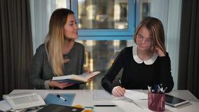 Een gelukkige leraar of een moeder onderwijzen een schoolmeisje Lees boek Het schoolmeisje schrijft in oefenboek Het glimlachen F stock footage