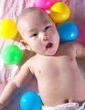 Een gelukkige 3 maanden oudbaby in een bad van ballen stock fotografie