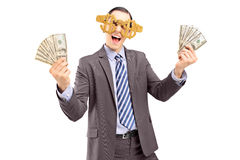 Een gelukkige mens die de glazen van het dollarteken dragen en Amerikaanse dollars houden Stock Fotografie