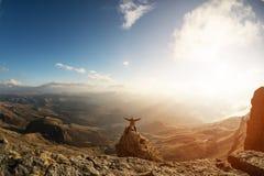 Een gelukkige mens met zijn omhoog hoge handen bevindt zich bovenop een afzonderlijk bevindende rots die boven de wolken tegen is Stock Afbeelding