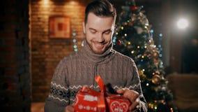 Een gelukkige mens ontvangt Kerstmis huidig in het rode verpakken stock video