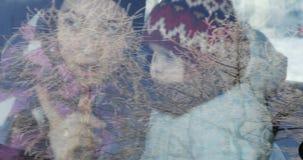 Een gelukkige moeder en een zoon zitten in de auto achter het glas en bekijken met verrassing het venster in de winter stock footage
