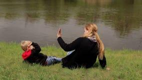 Een gelukkige moeder met haar zoon ligt op het groene gras op rivierbank in de lente stock videobeelden