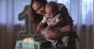 Een gelukkige moeder met haar zoons blazende kaarsen op een mooie cake stock footage