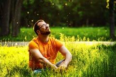 Een gelukkige nadenkende escapistmens zit op groen gras in park Royalty-vrije Stock Foto