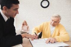 Een gelukkige oude mens ondertekent een contract, zit een vrouw erachter en spreekt op de telefoon royalty-vrije stock foto's