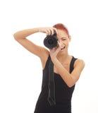 Een gelukkige roodharigefotograaf die met een camera ontspruiten stock afbeeldingen