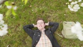 Een gelukkige student rust in de schaduw van de lentebomen na succesvolle dag stock video