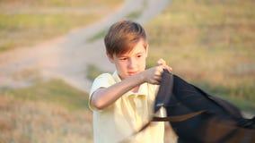 Een gelukkige tiener spint een rugzak rond hem De jongen verheugt zich begin de schooldag stock video