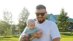 Een gelukkige vader houdt een zoon in zijn wapens stock video