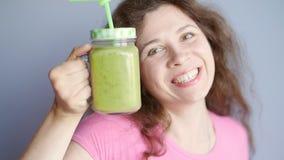 Een gelukkige vrouw houdt een groene smoothie in haar handen stock videobeelden