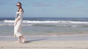 Een gelukkige vrouw loopt langzaam op een zandig strand langs het overzees stock video