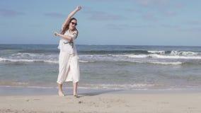 Een gelukkige vrouw spint en heft omhoog langzaam haar wapens op het strand op stock videobeelden
