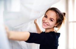 Een gelukkige vrouwelijke student die zich door venster bevinden, die gordijn houden royalty-vrije stock foto's