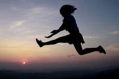 Een gelukkige vrouwensprong bij de zonsondergang Stock Afbeelding