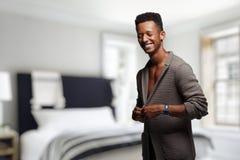 Een gemengde raskerel in bruine cardigan, probeert om op een vage slaapkamerachtergrond te ontkleden De ruimte van het exemplaar royalty-vrije stock foto's