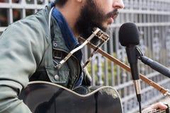 Een gemengde rasmens het spelen gitaar in de straat stock foto's
