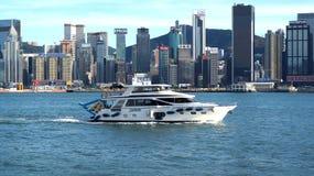 Een genoegenjacht in Victoria Bay en wolkenkrabbers van het Eiland Hong Kong Mening van de dijk Tsim Sha Tsui, Hong Kong, CH Stock Foto