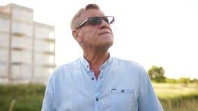 Een gepensioneerde buiten de stad is zenuwachtig en rokend Problemen van pensioneringsleeftijd Kwaad aan het roken stock footage