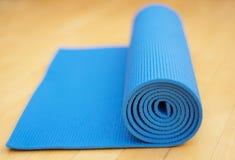 Een gerolde blauwe oefeningsmat voor Yoga of Pilates op houten vloer Stock Afbeelding