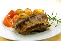 Een geroosterd zogend varken met aardappels en salade Royalty-vrije Stock Afbeeldingen