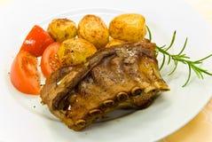 Een geroosterd zogend varken met aardappels en salade Stock Foto
