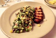 Een geroosterde bacon en een salade met gehakte sla, groene erwten, graan en wortelen dienden op een plaat als voorgerecht stock afbeelding
