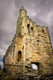Een geruïneerde toren van een kasteel met onweerswolken stock foto's