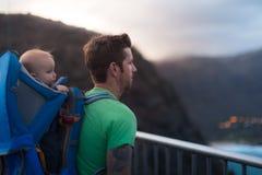 Een geschikte wandelaar die zich bovenop een berg bevinden die de mening bekijken Het uitoefenen met jonge geitjes traveling royalty-vrije stock foto's