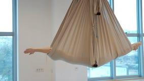 In een gesloten hangmat voor yoga in de lucht, ligt een vrouw en schommelt stock footage