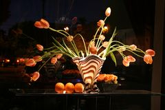 Een gestreept-gestreepte vaas met tulpen Stock Foto