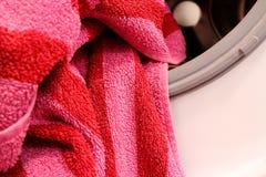Een gestreepte badhanddoek ligt op de rand van een wasmachinetrommel stock foto's