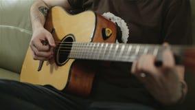 Een getatoeeerde mens die de gitaar spelen stock videobeelden