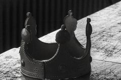 Een gevallen leider: close-up van een lijsthoogtepunt van taaie besluiten en een uitgeputte plastic gouden kroon in zwart-wit stock foto's