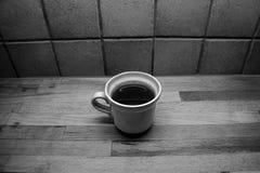 Een gevulde kop thee bevindt zich op houten countertop voor een betegelde muur royalty-vrije stock afbeeldingen