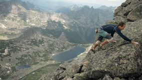 Een gewaagde jonge mannelijke klimmer beklimt op rotsen stock footage
