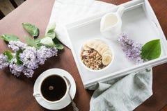Een gezond ontbijt met een kop van koffie, muesli, bananen en decor met bloemen van sering in een buitenhuis Stock Foto