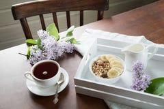 Een gezond ontbijt met een kop van koffie, muesli, bananen en decor met bloemen van sering in een buitenhuis Stock Foto's