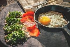 Een gezond Ontbijt van het land van roereieren in ronde pan en knapperige broden met zachte ricottakaas en verse kruiden stock afbeelding