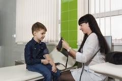 Een gezondheidsarbeider bereidt een tonometer voor om de druk van de jongen te meten royalty-vrije stock foto