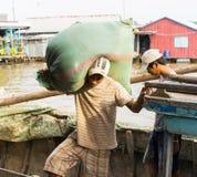 Een Giang, Vietnam - 29 Nov., 2014: De arbeider draagt zware zak ver vissenvoedsel van kleine houten vervoersboot aan het drijven Royalty-vrije Stock Fotografie